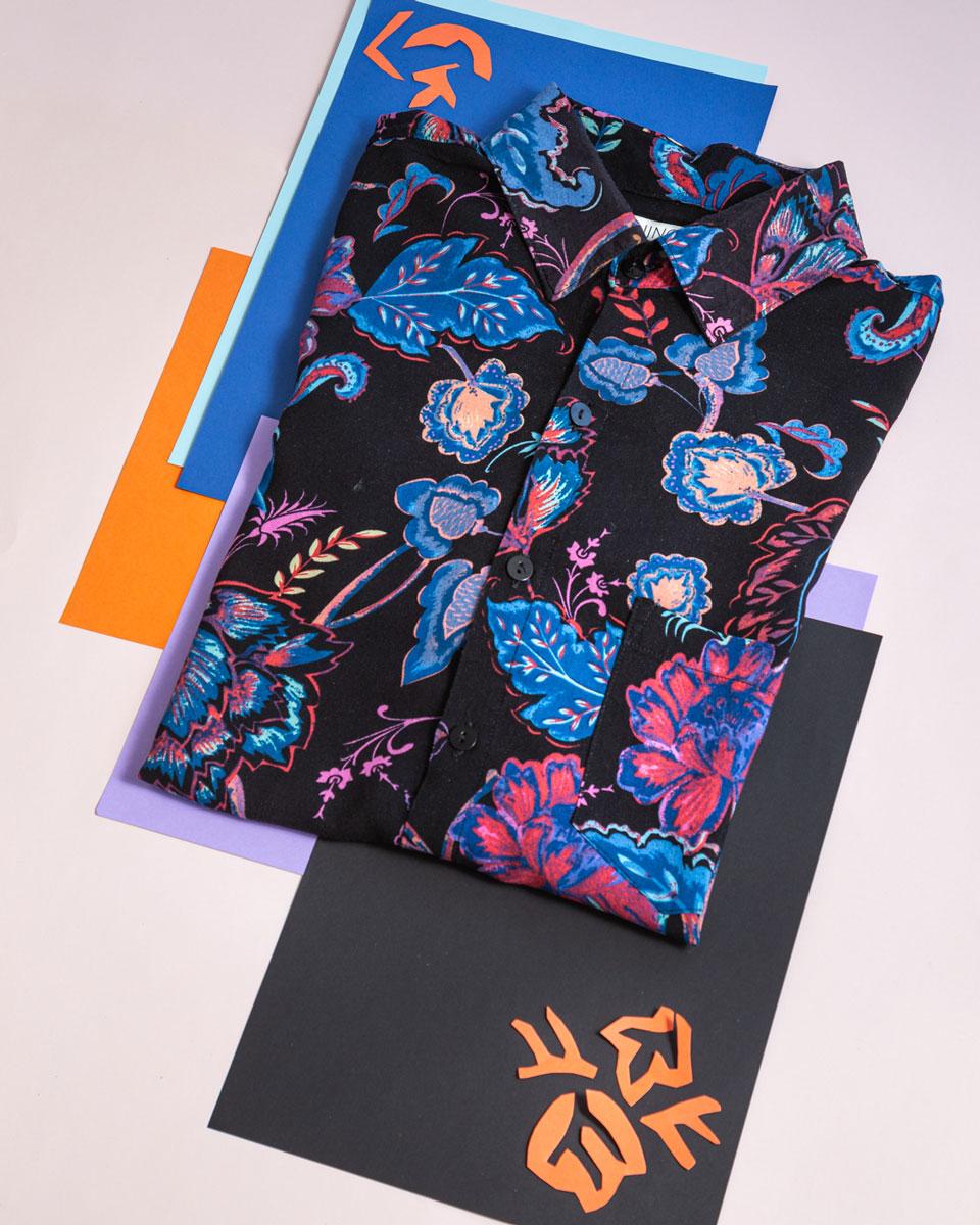 Foto arte de camisa estampada con fondo negro, flores rojas y azules. Detalles en naranja y arte. Kurosawa