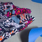 Artistic photo of printed shirt with striped pattern, shapes in dark blue, red, pink, orange and white