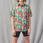 Woman with shirt printed with green, light blue and orange shapes