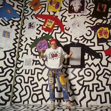 Foto de Haring con su obra pintada en el fondo