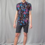Photo of man with black short sleeve shirt printed with electric blue flowers