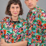 Photo of male and female couple with unisex shirts printed on board, green and orange