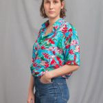 Young woman in light blue short-sleeved shirt with red birds print